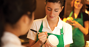 Starbucks partner writing name on take away cup