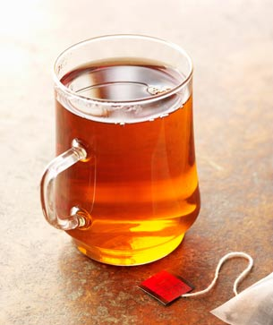 Glass mug of brewed tea and bag of tea