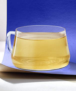 Brewed tea in glass cup with purple background